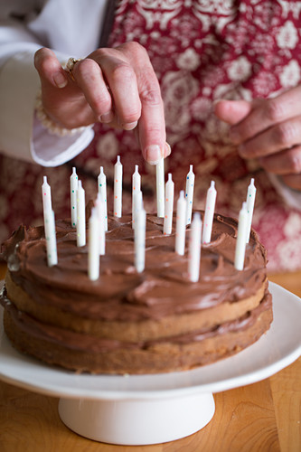 A birthday cake being decorated with candles