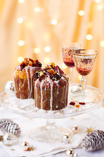 Mini fruit cakes topped with dried fruit and drizzled with icing, served on a cake stand alongside Christmas cocktails
