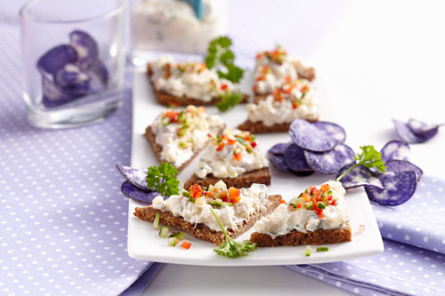 Wholemeal carnival snacks with soused herring cream and blue crisps