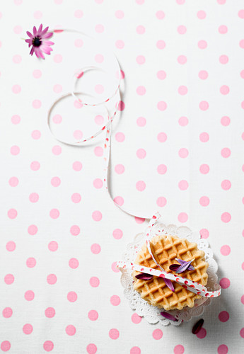 Waffle biscuits with a ribbon on a polka dot table cloth (seen from above)