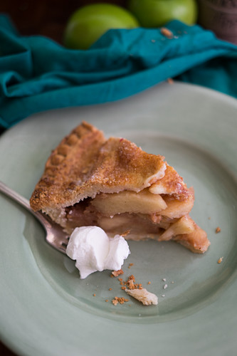 A piece of apple pie with cream