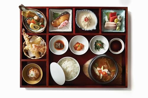 Verschiedene asiatische Gerichte auf Holztablett mit Fächern (Aufsicht)