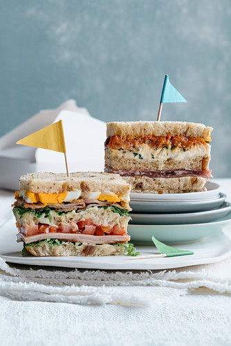 Club sandwiches with ham, burrata and cherry tomatoes, and with turkey ham, bacon and egg