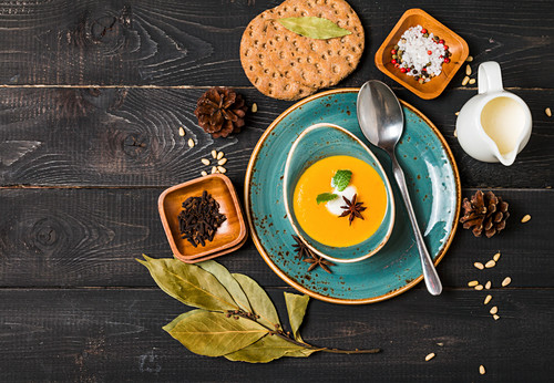 Pumpkin and carrot soup with cream and seasoning in blue bowl on black wooden background, top view
