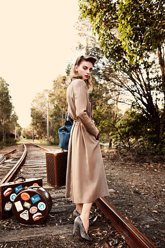 A young woman wearing a long coat standing on railway tracks with suitcases