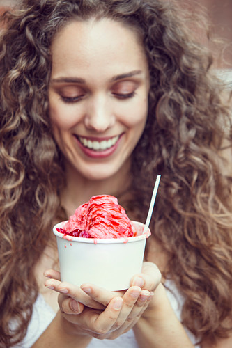 A young woman eating snow ice cream with strawberries