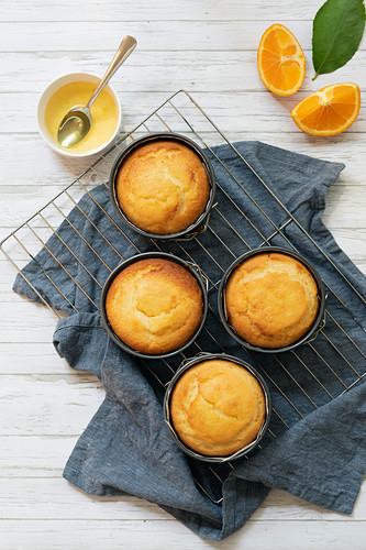 Four small round individual orange cakes in their tins cooling on a wire rack with a bowl of orange syrup