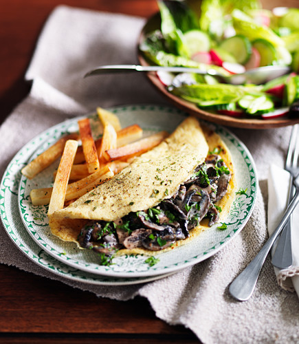 Omelette with mushrooms, peppers, french fries and salad