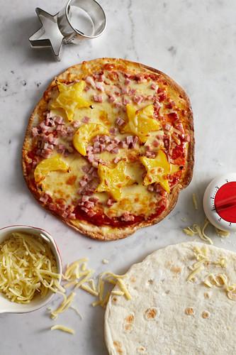 Pizza mit Schinken und Ananassternen