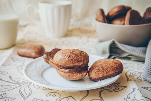 Chocolate glazed soft gingerbread cookies on a white plate, bowl of cookies, and milk