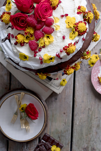 Chocolate cake with eatable flowers yellow and red roses, raspberries and whipped cream on a wooden table with plates