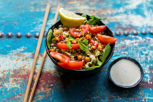 Quinoa salad with cauliflower, chickpeas, spinach, tomatoes and yoghurt