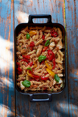 Fusilli with chicken, pepper and basil in a baking dish (seen from above)