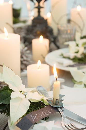 Weihnachtstisch mit weissen Weihnachtssternen, Kerzen und Christbaumkerzenhalter auf Besteck mit Namensschild