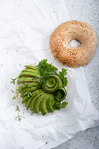 A sesame bagel with almond cheese, avocado, cucumber and fresh herbs (vegan)