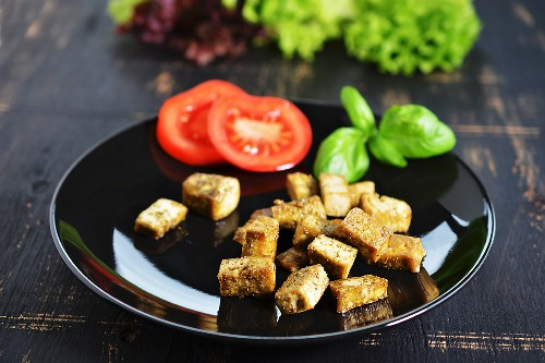 Diced tofu fried with herbs and garnished with tomatoes and basil