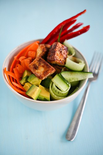 A bowl of sushi with tofu and vegetables