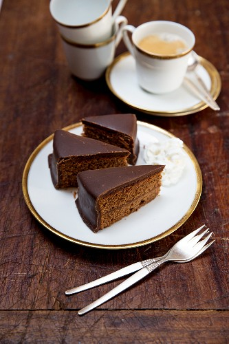 Sachertorte (rich Austrian chocolate cake) with whipped cream and a cup of coffee