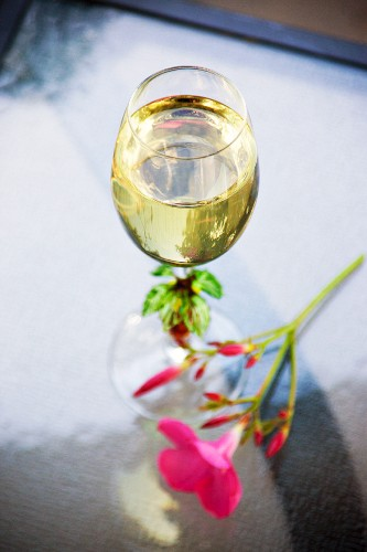 A pink flower next to a glass of white wine