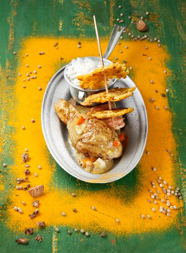 Curried chicken with plantain crisps and rice (Spain)