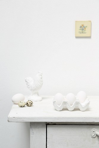 White eggs in egg box, quail eggs and cockerel ornament on top of cabinet
