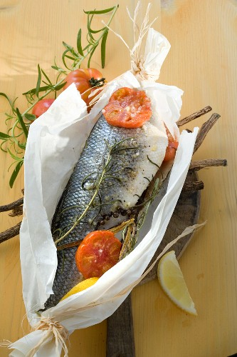 Fish in parchment paper with liquorice, herbs and tomatoes