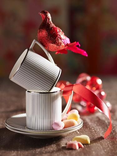 Tassen mit rotem Dekovogel und Geschenkband dekoriert