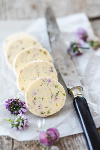 Chive flower butter on a piece of paper with a knife