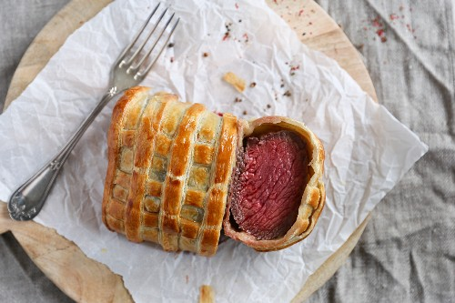 Beef Wellington, sliced, on a piece of paper (seen from above)