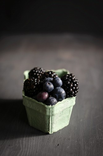 Blueberries and blackberries in an old-fashioned cardboard punnet