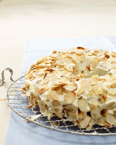 Frankfurt wreath cake with flaked almonds on a wire rack