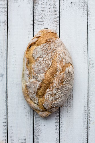 A loaf of rustic bread on a wooden surface
