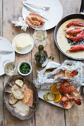The remains of lobster, bread and wine after a meal