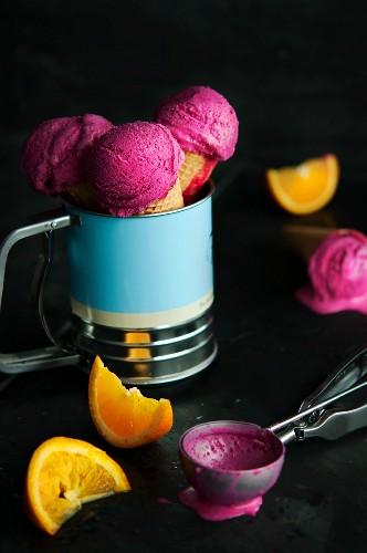 Raspberry ice cream in cones with an ice cream scoop and orange wedges