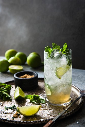 A mojito made with limes, brown sugar and mint on a tray