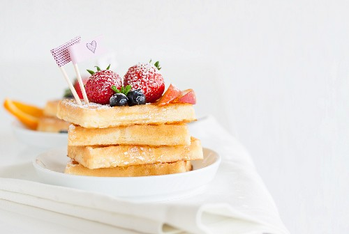 A stack of waffles with fresh fruit and agave syrup