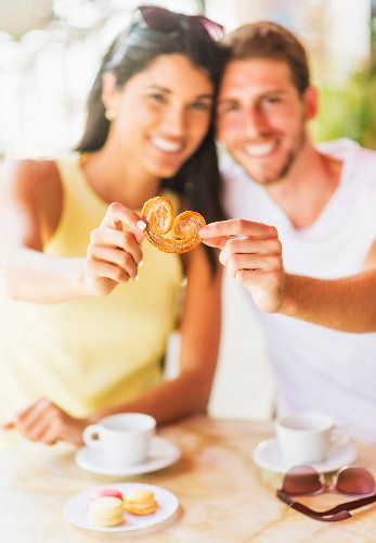 A couple in a cafe sharing a biscuit