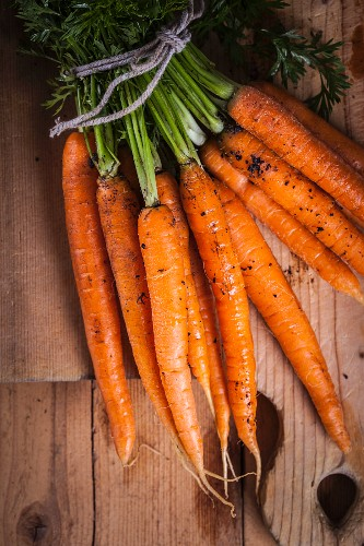 A bundle of fresh carrots on a wooden board