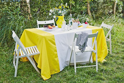 A homemade yellow and white tablecloth on a summery table outdoors
