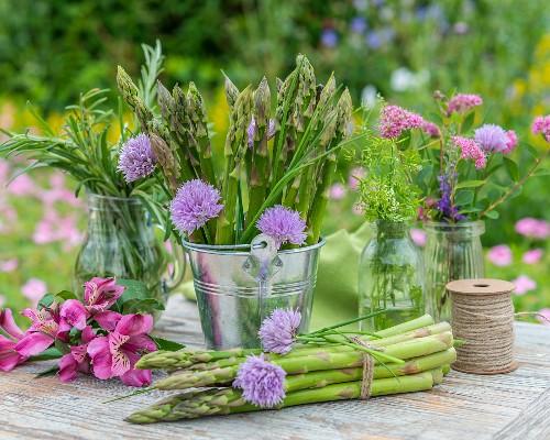 Green asparagus and fresh herbs on a garden table