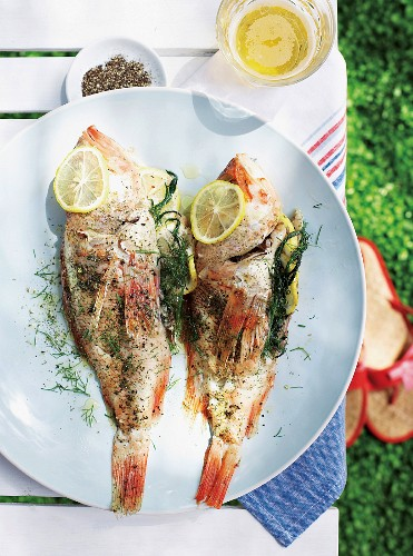 Two fish, grilled in paper, with herbs and lemons