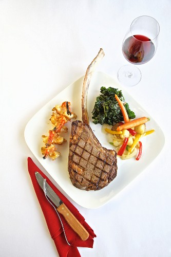 Grilled tomahawk steak with side dishes and a glass of red wine (seen from above)