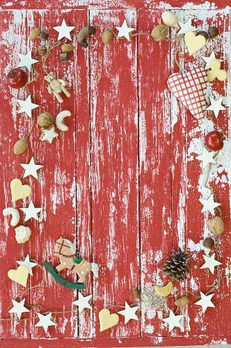 Rahmen aus weihnachtlicher Deko, Nüssen und Plätzchen auf rot-weißem Untergrund