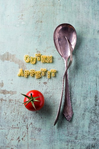 The words 'Guten Appetit' spelt with alphabet pasta next to cutlery and a tomato