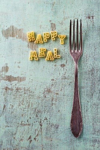 The words Happy Meal made from alphabet pasta next to a fork