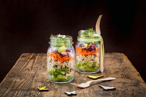 Springtime layered salad with rice, vegetables and daisies in jars