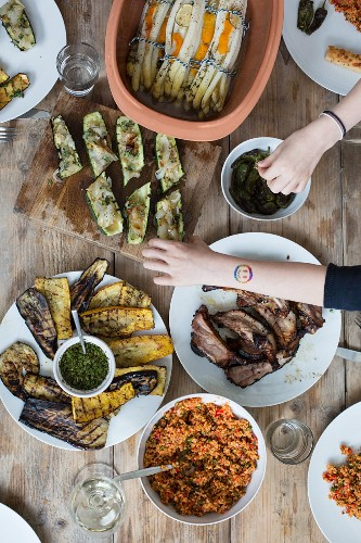 Group spare ribs, vegetables, salads and sauces on a wooden table (seen from above)