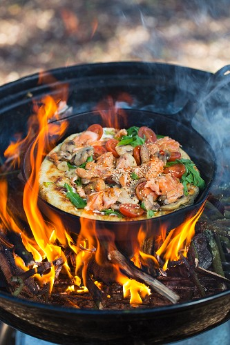 A salmon pizza being baked over an open fire