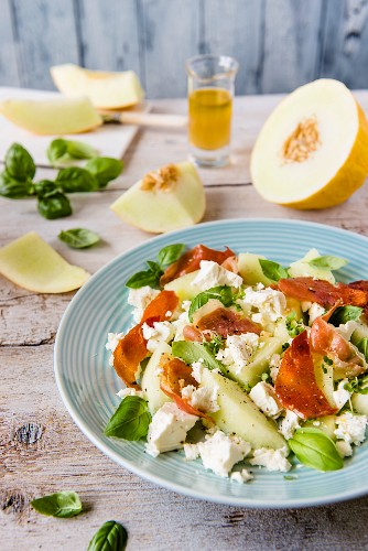 Melon salad with feta cheese, Parma ham, basil leaves and dressing