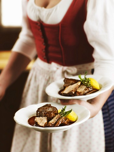 A woman in a traditional dirndl dress serving a tri-tip steak in red wine sauce